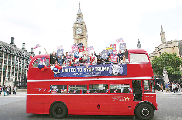 Activists wave US flags as they ride on a 'Stop Trump' battle bus as they pass the Houses of Parliament in London on Sept 21 in a campaign run by campaign group Avaaz to mobilise US expatriots in the UK to register to vote in the US presidential election. Voters are set to go to the polls to elect the 45th president of the US on Nov 8. (AFP)