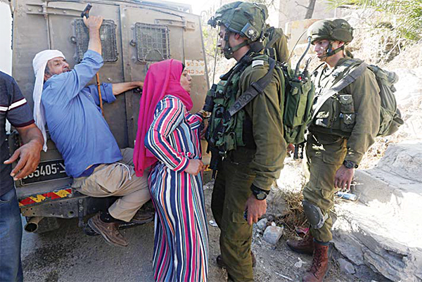 Palestinian demonstrators confront Israeli soldiers, after they temporarily detained two Palestinian youth, in the West Bank village of Burin on Sept 15, following scuffles with Israeli settlers. (AFP)