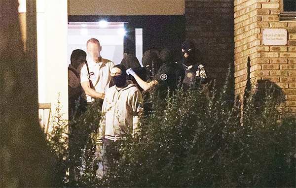 A woman (Centre hood) is taken out of a building in Boussy-Saint-Antoine south of Paris on Sept 8, where female suspects, said to have been planning new acts of violence, were arrested. (AFP)