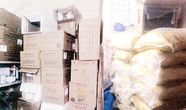 Cartons of milk and oil (left), and sacks of rice and sugar seized.