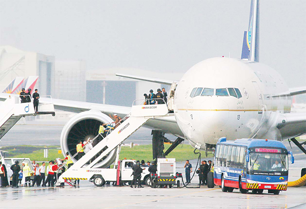 Passengers disembark from Saudi Arabian Airlines plane sitting on the runway of the Ninoy Aquino International Airport after it made a distress call shortly before landing on Sept 20, at suburban Pasay city south of Manila, Philippines. (AP)