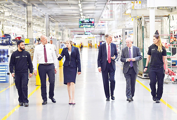 British Prime Minister Theresa May (center left), and Chancellor of the Exchequer, Philip Hammond (center right), speak to employees during a visit to the Jaguar Land Rover factory on Sept 1 in Solihull. Mrs May used the visit to highlight that Britain continues to be open for economic investment following the country's decision to leave the European Union. (AFP)