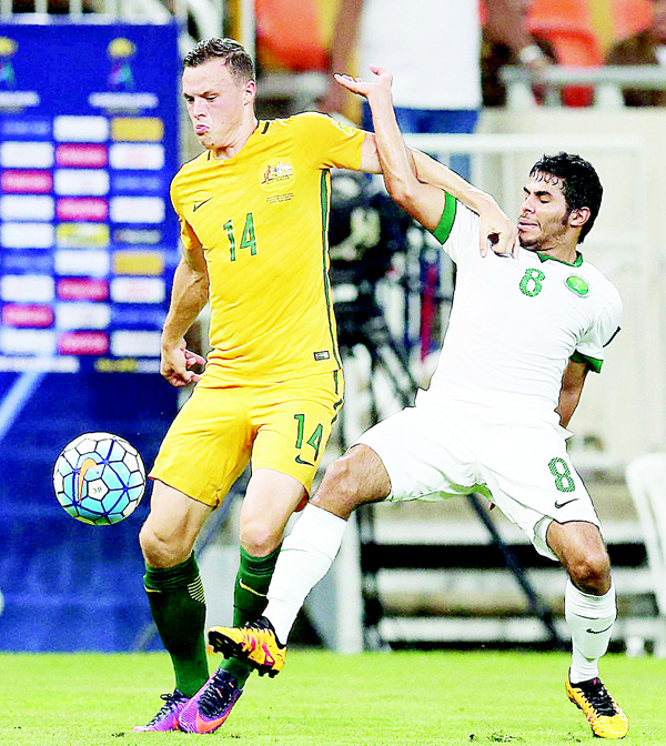 Australia's Brad Smith (left), is marked by Saudi's Yahia Alshehri (right), during the 2018 FIFA World Cup Qualifiers match between Saudi Arabia and Australia at the King Abdullah Sports City Stadium in Jeddah on Oct 6. (AFP)