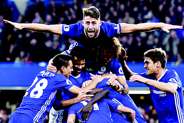 Chelsea's English defender Gary Cahill (top) jumps onto the huddle to join the celebrations after Chelsea's French midfielder N'Golo Kante scored their fourth goal during the English Premier League football match between Chelsea and Manchester United at Stamford Bridge in London on Oct 23. (AFP)