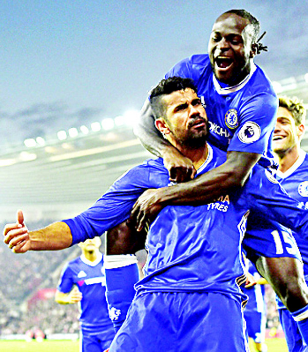 Chelsea's Brazilian-born Spanish striker Diego Costa (center), celebrates scoring their second goal with Chelsea's Nigerian midfielder Victor Moses (top), during the English Premier League football match between Southampton and Chelsea at St Mary's Stadium in Southampton, southern England on Oct 30. (AFP)