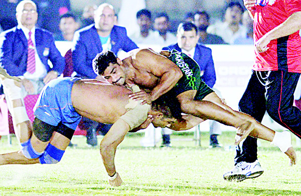 This file photograph taken on May 6, 2016, shows a Pakistan kabaddi player (right), being tackled by an Indian opponent during their final match of the 3rd Asian Kabaddi Circle Style Championship 2016 in Wah some 45 kms from Islamabad. (AFP)