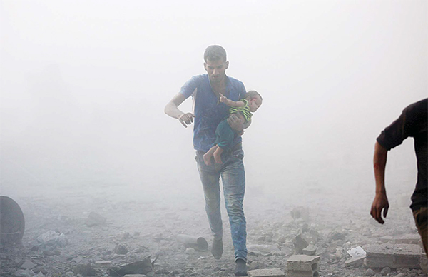 A Syrian man carrying a child emerges from a dust cloud following a reported airstrike on Kafr Batna, in the rebel-held Eastern Ghouta area, on the outskirts of the capital Damascus, on Sept 30. Air raids on several rebel-held towns in the Eastern Ghouta region killed at least 17 people including eight children, the Syrian Observatory for Human Rights monitor said. (AFP)