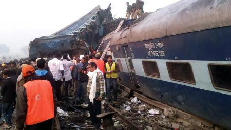 Indian rescue workers search for survivors in the wreckage of a train that derailed near Pukhrayan in Kanpur district on November 20, 2016