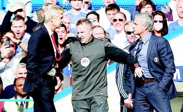 This file photo taken on October 5, 2014 shows Chelsea's Portuguese manager Jose Mourinho (right) and Arsenal's French manager Arsene Wenger (left) being kept apart by the fourth official Jonathan Moss during the English Premier League football match between Chelsea and Arsenal at Stamford Bridge in London on October 5, 2014. (AFP)