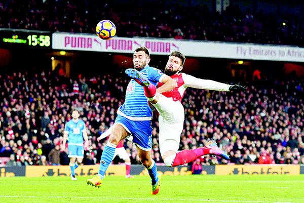 Arsenal's French striker Olivier Giroud (right), has an unsuccessful shot defended by Bournemouth's English defender Steve Cook during the English Premier League football match between Arsenal and Bournemouth at the Emirates Stadium in London on Nov 27. (AFP)