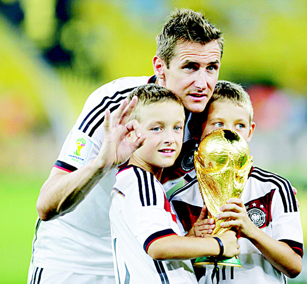 The July 13, 2014 file photo shows Germany's Miroslav Klose posing with the World Cup trophy and his sons following their 1-0 victory over Argentina after the World Cup final soccer match between Germany and Argentina at the Maracana Stadium in Rio de Janeiro, Brazil. The German soccer federation says on Nov 1, striker Miroslav Klose, the top scorer in World Cup history, is ending his playing career and will train as a coach. (AP)