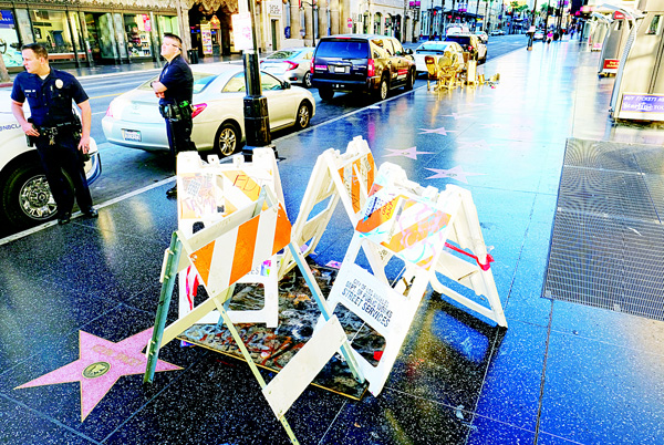 Los Angeles police officers stand by the Hollywood star for Donald Trump on the Hollywood Walk of Fame, on Nov 9, in Los Angeles. Officials hope to unveil Trump's repaired star as soon possible now that he's elected president. The star remains blocked off and covered in plywood two weeks after a protester was arrested for taking a sledgehammer to it. The man was charged with felony vandalism. (AP)