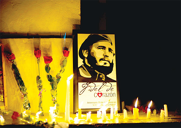 An image of the late Cuban leader Fidel Castro, surrounded by candles and roses, leans against a wall of the university where Castro studied law as a young man, during a students' vigil in Havana, Cuba on Nov 26. (AP)