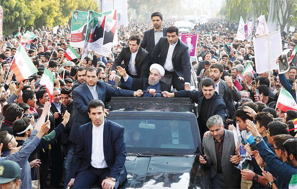 In this photo released by an official website of the office of the Iranian Presidency, Iranian President Hassan Rouhani (center), waves to his well-wishers from his car during a public welcoming ceremony for him upon his arrival in Karaj, 21 miles (35 kms) west of the capital Tehran, Iran on Nov 16. Rouhani says his country will remain committed to a landmark nuclear deal with world powers regardless of the US presidential election result. (AP)
