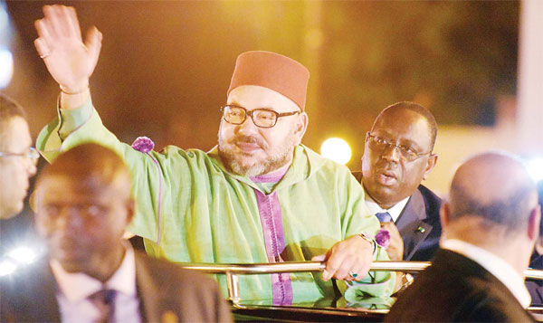 Moroccan King Mohammed VI (center), waves to the crowd eyed by Senegalese President Macky Sall (right), upon his arrival at Dakar's Airport at the starts of his state visit, on Nov 6. (AFP)