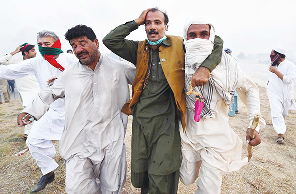 Supporters of opposition party Tehreek-i-Insaf (PTI) run from tear-gas shells during clashes with police, in Swabi on Oct 31. Police in Pakistan fired tear-gas on thousands of opposition supporters who tried to remove barricades while marching towards capital Islamabad, an AFP reporter said. (AFP)