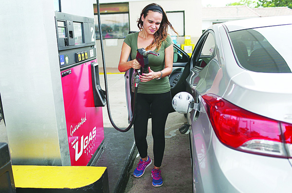 In this file photo, Wendy Yanez fills her vehicle with gas at a U-Gas station in Miami, Florida. As gas prices remain low across the nation, a recent study released by JPMorgan Chase Institute, indicates that as American consumers have more income to spend they use some of that money to purchase higher-octane gas that costs more thus negating the money saved even as gas prices remain low. (AFP)