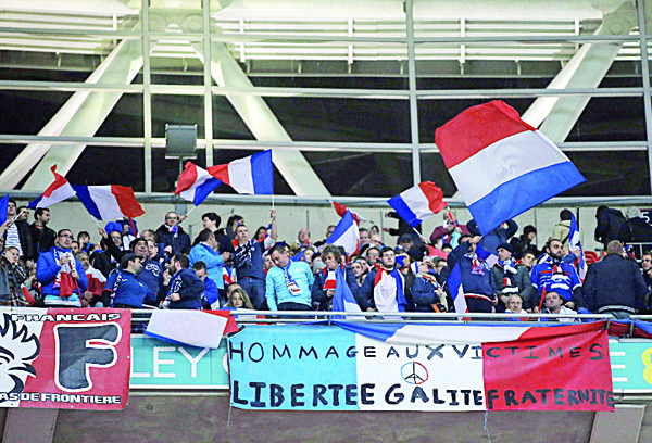 Football fans wave French flags before the start of the friendly football match between England and France at Wembley Stadium in West Londan on Nov 17. (AFP)