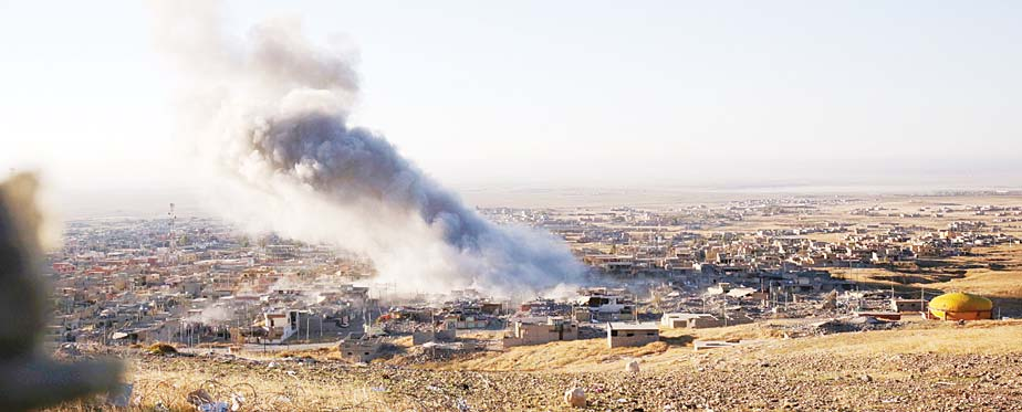 Smoke believed to be from an airstrike billows over the northern Iraqi town of Sinjar on Nov 12. Kurdish Iraqi fighters, backed by the US-led air campaign, launched an assault Thursday aiming to retake the strategic town of Sinjar, which the Islamic State overran last year in an onslaught that caused the flight of tens of thousands of Yazidis and first prompted the US to launch airstrikes against the militants. (AP)