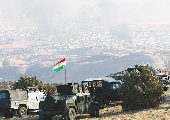 Iraqi Kurdish forces are seen stationed on a hilltop as smoke billows during an operation by Iraqi Kurdish forces backed by US-led strikes in the northern Iraqi town of Sinjar on Nov 12, to retake the town from the Islamic State group and cut a key supply line to Syria. (AFP)