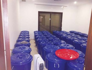 A large number of plastic barrels filled with local liquor are kept in a room to cook at certain temperature