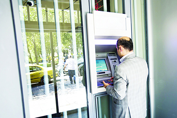 An Iranian man withdraws cash from an ATM machine in the capital Tehran on July 28. Iran's finance minister says Tehran was prepared to deal with the economic impact of oil prices as low as $30 per barrel. (AFP)