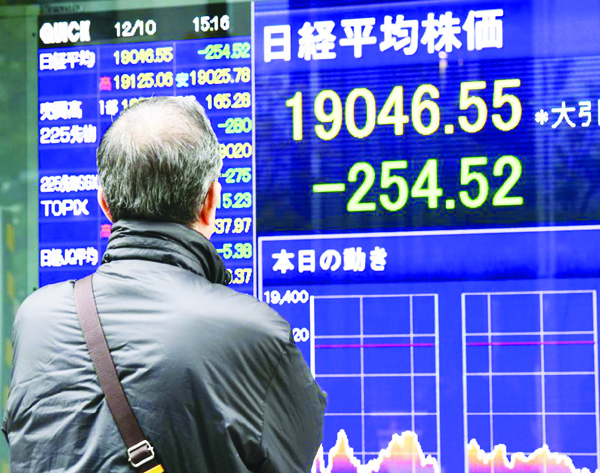A man looks at a share prices board illustrating the numbers of the Tokyo Stock Exchange in Tokyo on December 10. Japan stocks closed lower as Nikkei falls to 20.63 points on Dec 25. (AFP)