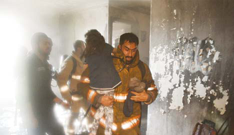 A fireman carries a child to safety.