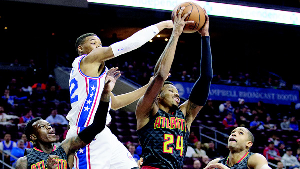 Atlanta Hawks' Kent Bazemore (center right), pulls down the rebound with Philadelphia 76ers' Richaun Holmes (center left), reaching from behind as Hawks' Dennis Schroder (left), and Al Horford (right), watch during the first half of an NBA basketball game on Jan 7, in Philadelphia. (AP)