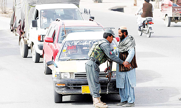 An Afghan policeman searches a passenger at a checkpoint in Kandahar, Afghanistan on Jan 26. An Afghan official says that a policeman has turned his weapon on fellow police officers at a checkpoint in the country's south, killing 10 policemen. (AP)