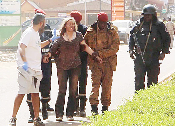 This image taken from AP television shows a woman being led to safety in Ouagadougou, Burkina Faso, on Jan 16. The overnight seizure of a luxury hotel in Burkina Faso's capital by al-Qaeda-linked extremists ended Saturday when Burkina Faso and French security forces killed four jihadist attackers and freed more than 126 people, the West African nation's president said