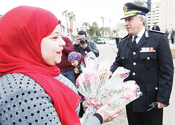 A woman gives out flowers to policemen on Police Day, which is also the anniversary of the 2011 uprising, in Tahrir Square, Cairo, Egypt on Jan 25. (AP)