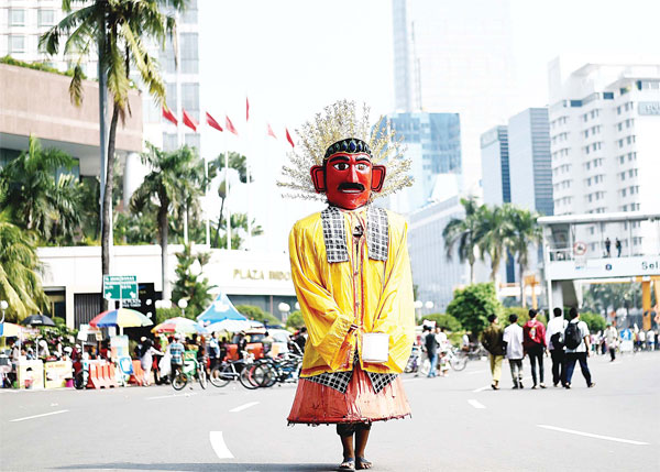 An Indonesian man dressed in a traditional costume walks on the road as people observe a 'car free Sunday' in Jakarta on Jan 17, as life for the capital's residents returns to normal following the deadly gun and bomb attacks that rocked the city on Jan 14. (AFP)
