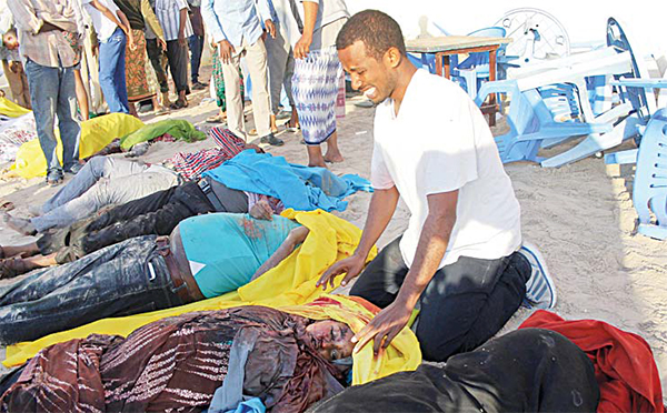 A Somali man cries after identifying the dead body of his sister on the beach following an overnight attack on a beachfront restaurant in Mogadishu, Somalia on Jan 22. (AP)