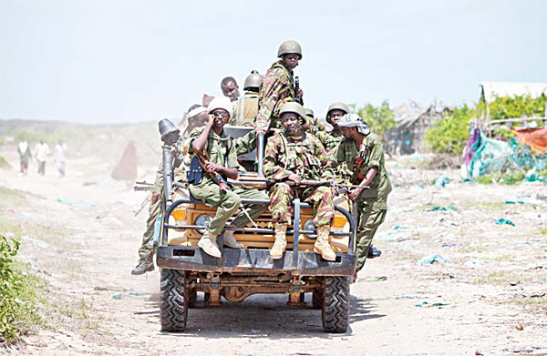 Kenyan army soldiers, wearing helmets, and members of a pro-government Somali militia ride on a truck in the seaside town of Bur Garbo, Somalia
