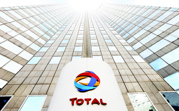 In this file photo, the logo of the French oil giant Total SA is seen at the entrance of the company headquarters in the La Defense business district, west of Paris. (AP)