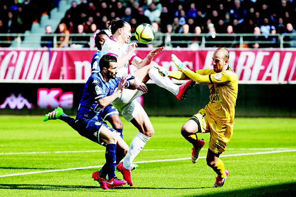 PSG's Zlatan Ibrahimovic (center), challenges for the ball with Troyes' Matthieu Saunier (left), and Troyes' goalkeeper Matthieu Dreyer (right), during their League 1 soccer match between Paris Saint-Germain and Troyes, in Troyes, France on March 13. Zlatan Ibrahimovic scored four second-half goals as Paris Saint-Germain clinched its fourth straight French league title in style, pulverizing last-place Troyes 9-0 on Sunday to become champion with a record eight games to spare. (AP)