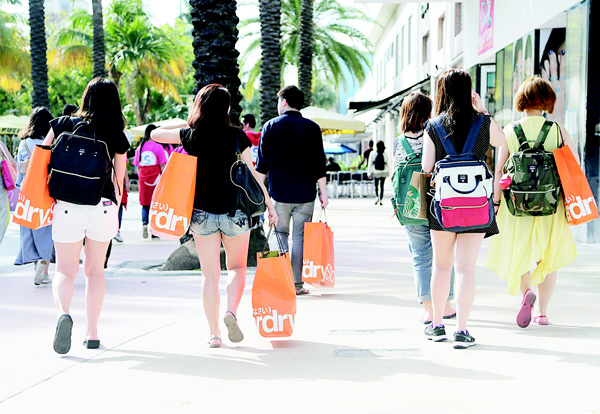 In this file photo, tourists from Taiwan carry shopping bags as they walk along Lincoln Road Mall, a pedestrian area featuring retail shops and restaurants in Miami Beach, Fla. On March 25, 2016, the Commerce Department revised the Q4 GDP growth to 1.4 pct. (AP)