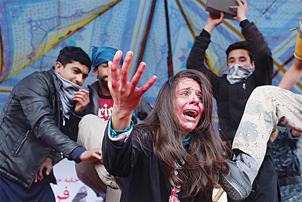 Afghan actors perform in a play depicting the 2015 lynching of Afghan woman Farkhunda, in Kabul on March 17. Farkhunda died on March 19, 2015 after being beaten with sticks and stones, thrown from a roof, run over with a car, set on fire, then dumped in a river, as police allegedly looked on, after being falsely accused of burning a Quran. (AFP)