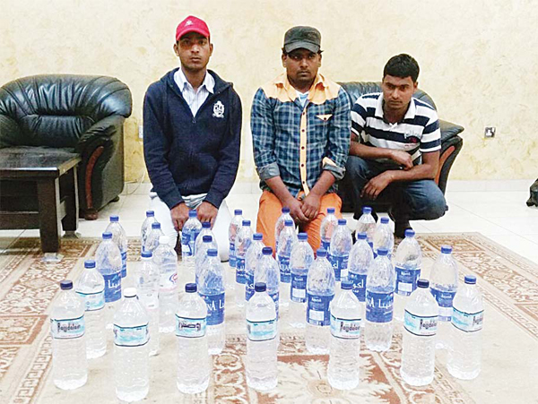 The trio with the seized local liquor bottles