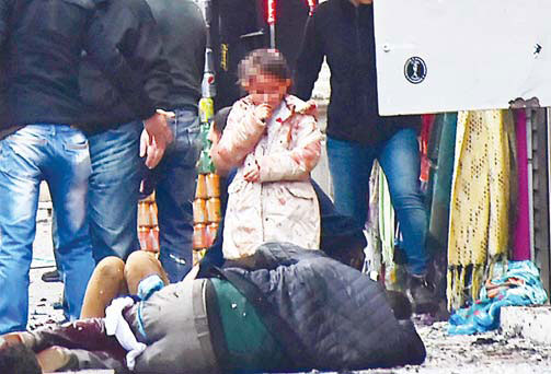 A girl with traces of blood on her clothes looks at victims of an explosion on Istikal Avenue, in Istanbul, Turkey on March 19