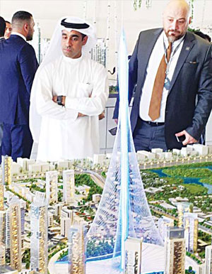Visitors look at a to-scale model of a new tower the real estate giant Dubai Emaar Properties plans to build that will break the record and be taller than the Burj Khalifa, currently the world's tallest tower, during an exposition in Dubai on April 10. (AFP)