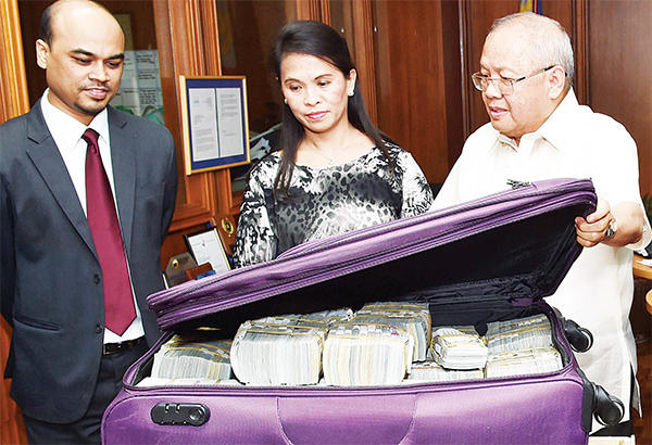 This photo provided by the Bangko Sentral ng Pilipinas, (from left), Second Secretary and Head of Chancery of the Bangladesh Embassy in Manila Probash Lamarong, Anti-Money Laundering Council (AMLC) Secretariat Executive Director Julia Bacay-Abad and AMLC Member and Insurance Commissioner Emmanuel Dooc open a bag containing US dollars that was returned by Chinese casino junket operator Kam Sin Wong to Bangladesh and Philippine AMLC officials in Manila, Philippines on March 31. (AP)