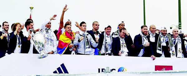 Real Madrid players hold up the trophy in celebration of the team's win at Plaza Cibeles in Madrid on May 29 after the UEFA Champions League final football match between Real Madrid CF and Club Atletico de Madrid held in Milan, Italy. (AFP)