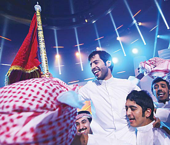 Kuwait's Rajih Al-Hamidani (center), celebrates after winning the fi nal of the televised program Million's Poet on May 17, at Abu Dhabi's Al-Raha Theatre. Apart from the glory, the Kuwaiti student took home fi ve million dirhams ($1.36 million), the top prize in a television show followed by millions of poetry lovers across the region. (AFP)
