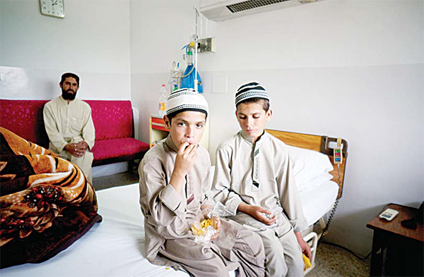 Pakistani children Abdul Rasheed, 9, (left), and Shoaib Ahmed, 13, sit in a room during a day at a hospital in Islamabad