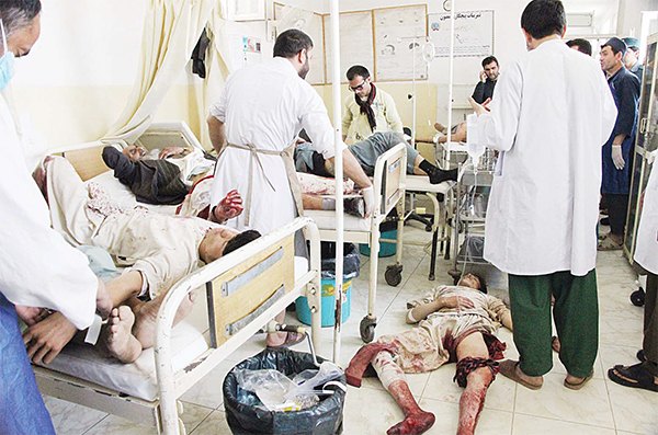 Afghan men who were injured after a motorcycle bomb exploded in a crowded market receive treatment at a hospital in Takhar province on June 20. (AFP)