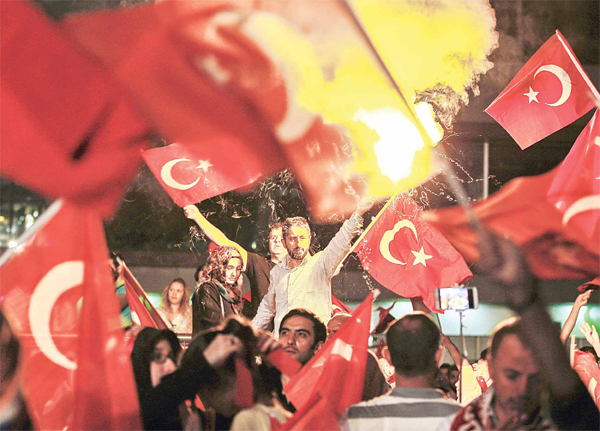 People light flares and wave Turkish flags as they gather in Taksim Square in Istanbul on July 18.