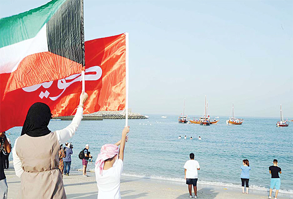 Old and new national flags greet the young sailors at finale of Kuwait's annual diving expedition. - Photo by Ghazy Gafaf – KUNA