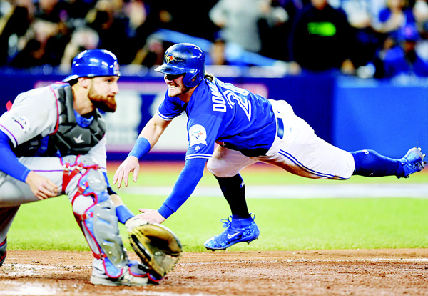 Toronto Blue Jays' Josh Donaldson slides in to score the winning run past Texas Rangers' catcher Jonathan Lucroy during tenth inning Game Three American League Division Series action, in Toronto on Oct 9. (AP)
